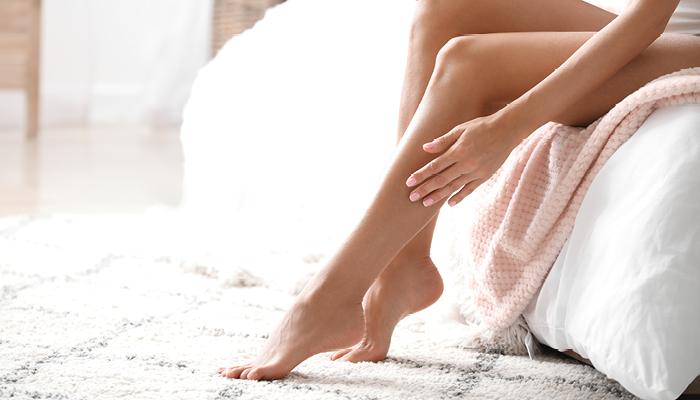 Donna che sfiora le sue gambe morbide