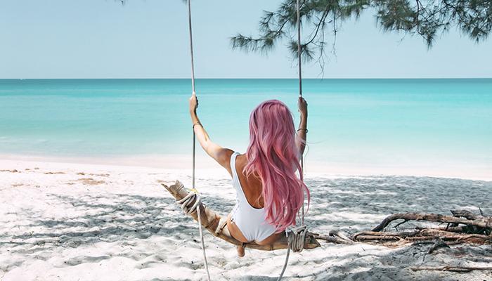Ragazza con capelli rosa su altalena in spiaggia